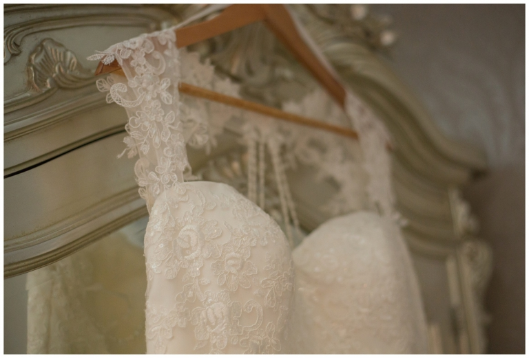 lace wedding dress hung on wardrobe