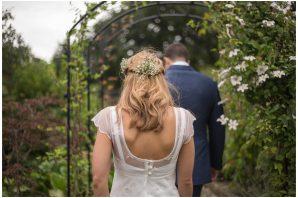 bride and groom walking in garden, flowers in brides hair as she walks away